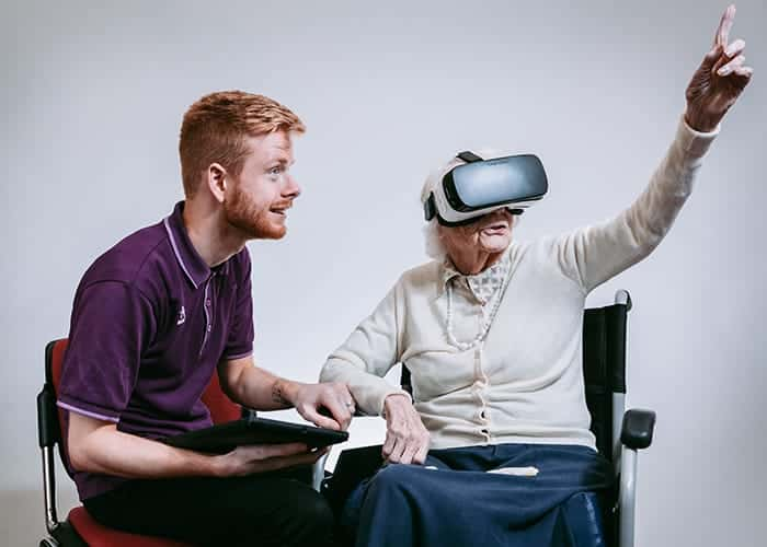 A resident and a staff member use virtual reality