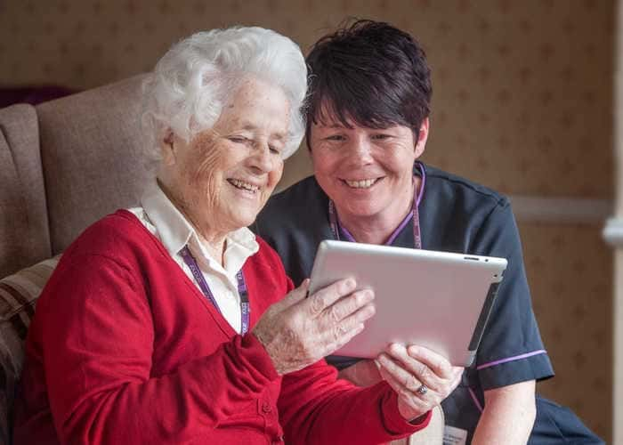 Carer and resident looking at an ipad