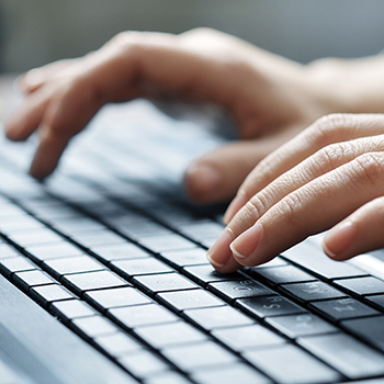 Hand typing on a computer keyboard