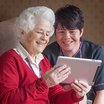 A carer with a resident looking at an iPad