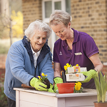 A carer and resident gardening