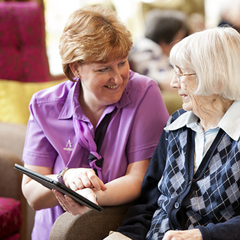 A carer and a resident reading