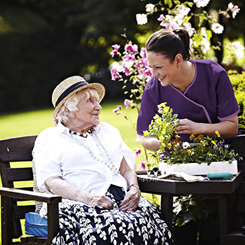 A carer and resident in the garden